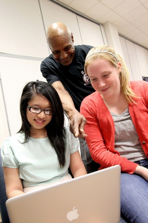 Three students looking at a laptop.