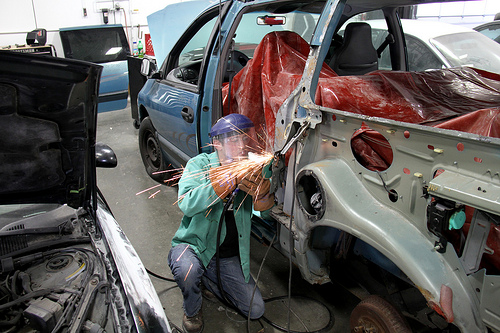 Auto collision repair student working on a car body