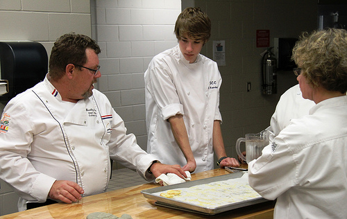 Culinary student taking dish out of oven
