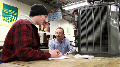 Student and HVAC instructor workin on air conditioning unit